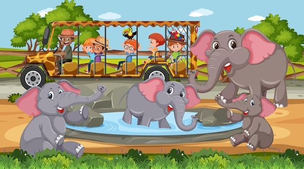 Groupe d'éléphants dans la scène safari pendant la journée avec des enfants dans la voiture de tourisme