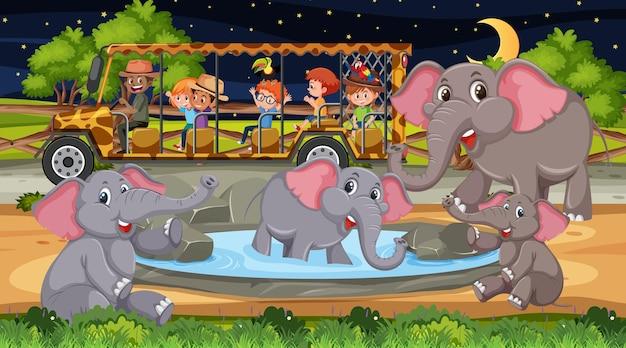 Groupe d'éléphants en scène safari avec des enfants dans la voiture de tourisme