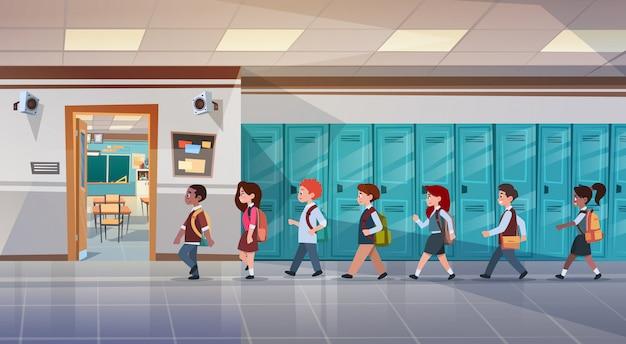 Groupe d'élèves marchant dans le couloir de l'école en salle de classe, élèves de race mixte