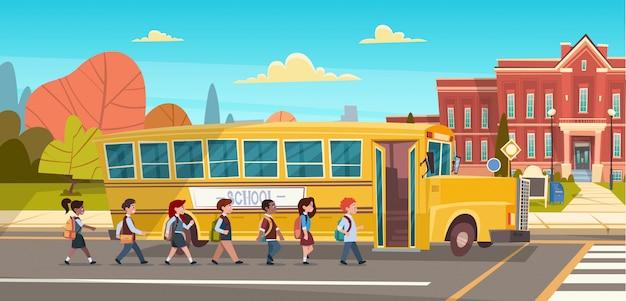 Groupe d'élèves mix race marche à pied pour bâtiment scolaire de bus jaune