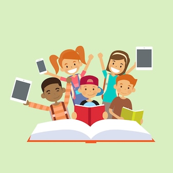 Groupe d'enfants d'âge scolaire avec un livre de lecture de gadgets intelligents modernes