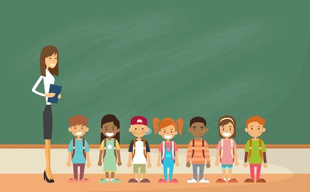 Groupe d'enfants d'âge scolaire avec le panneau vert de la salle de classe