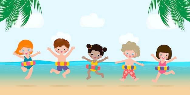 Groupe d'enfants en vêtements de natation avec des jouets gonflables sur la plage