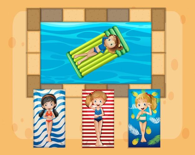 Un groupe de filles bronzant à côté de la piscine