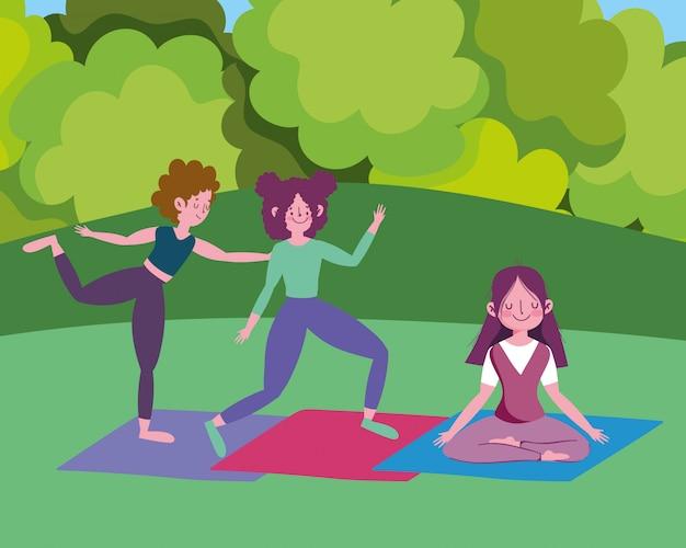 Groupe de filles heureuses pratiquant le yoga sur des tapis dans le parc