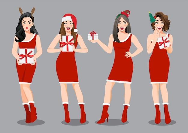 Groupe de filles de noël en robe rouge tenant le personnage de dessin animé de boîtes présentes