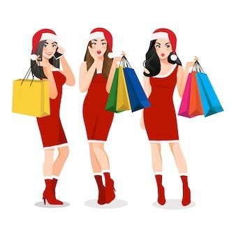 Groupe de filles de noël en robe rouge tenant le personnage de dessin animé de sacs à provisions
