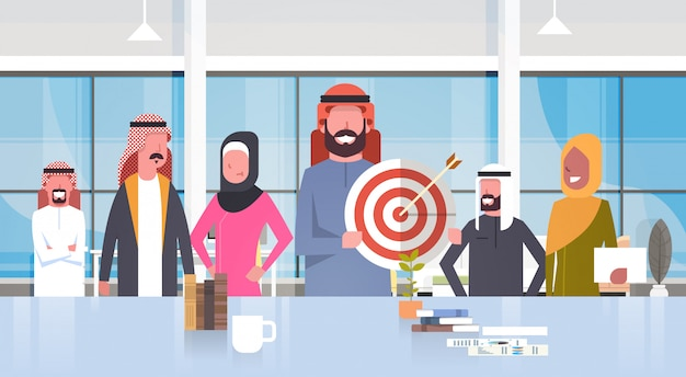 Groupe de gens d'affaires arabes dans le bureau moderne homme d'affaires tenir cible objectif équipe musulmane portant des vêtements traditionnels
