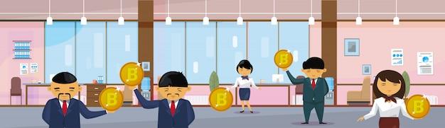 Groupe de gens d'affaires asiatiques détenant des bitcoins