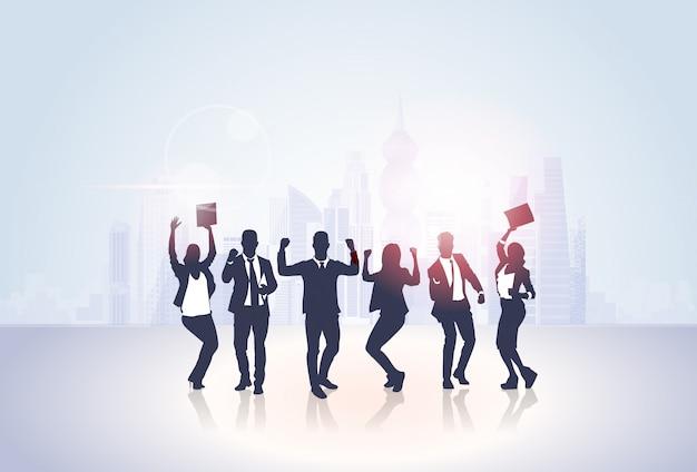 Groupe de gens d'affaires silhouette excité tenir les mains en l'air, bras levés, concept de gens d'affaires gagnant gagnant