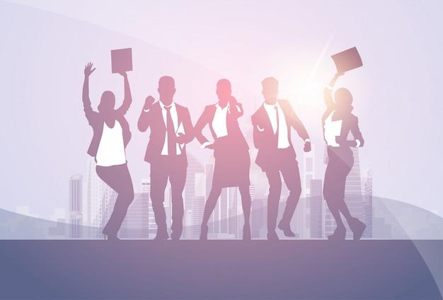 Groupe de gens d'affaires silhouette excité tenir les mains en l'air, bras levés, concept de gens d'affaires gagnant su