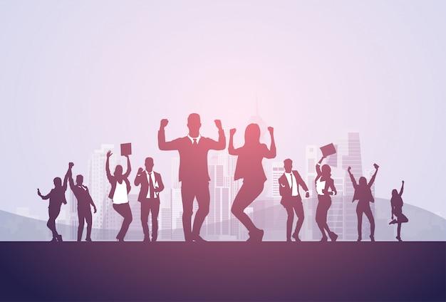 Groupe de gens d'affaires silhouette excité tenir les mains en l'air, bras levés