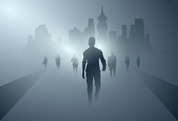 Groupe de gens d'affaires silhouette faisant le pas en avant sur toute la longueur sur fond d'ombre ville