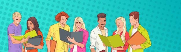 Groupe de jeunes étudiants lisant sur pop art coloré rétro