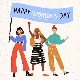 Groupe de jolies jeunes femmes, filles ou activistes féministes debout ensemble et tenant une bannière avec le souhait de la journée de la femme heureuse
