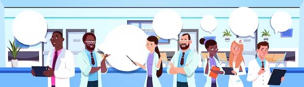 Groupe de médecins de race mixte debout sur un hôpital moderne
