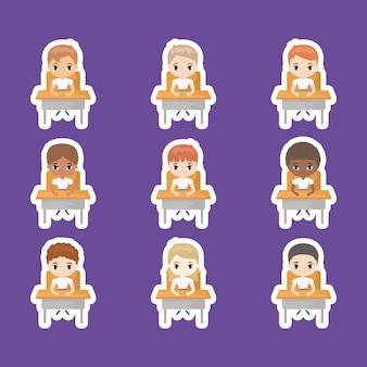 Groupe de mignons petits étudiants assis dans les pupitres d'école