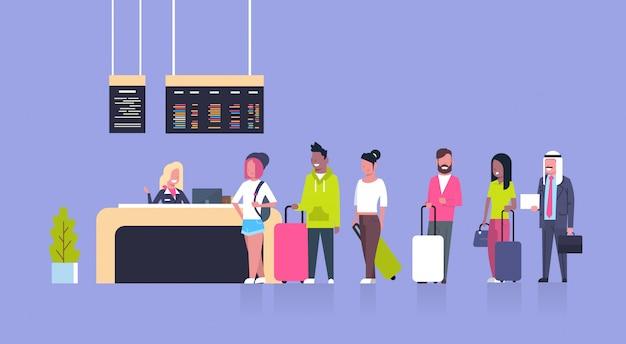Groupe de passagers de race mixte debout dans la file d'attente pour s'inscrire à l'aéroport, concept du tableau des départs