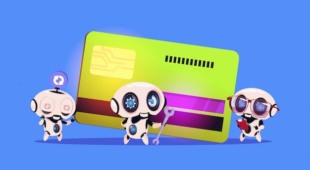 Groupe de robots se tenant debout sur le concept de paiement de technologie robotique de carte de crédit