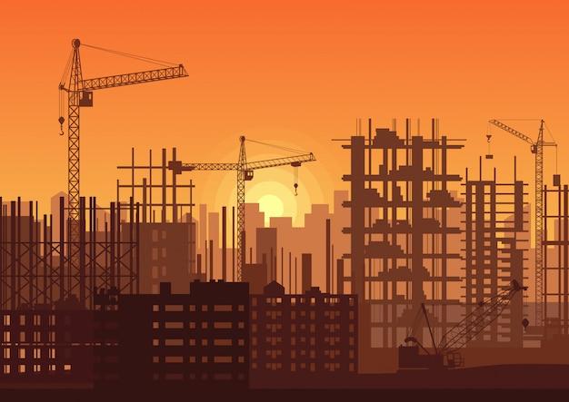 Grues à tour sur chantier de construction au coucher du soleil.