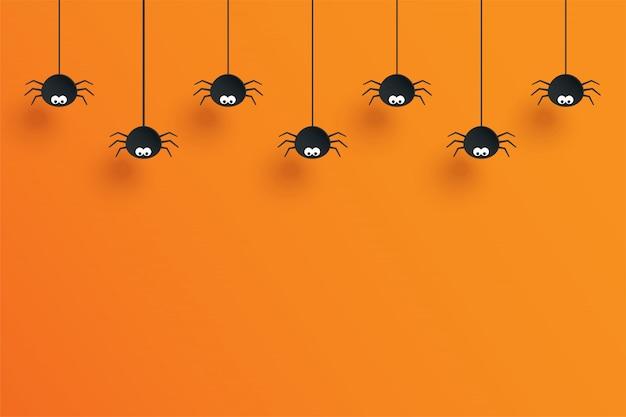 Halloween avec araignées suspendues et fond orange