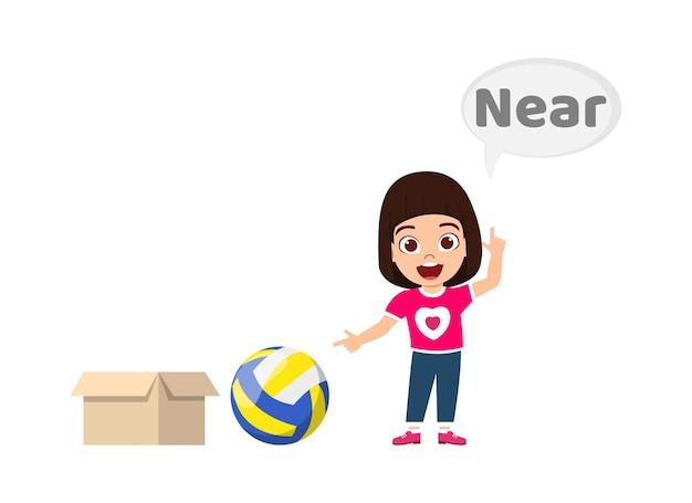 Happy cute kid girl avec ballon et carton, apprentissage du concept de préposition, près de préposition et pointage isolé