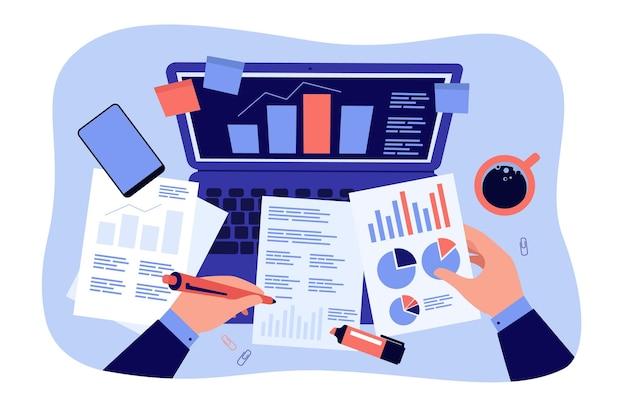 Haut du lieu de travail de bureau, mains du comptable analysant et étudiant l'illustration