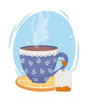 L'heure du thé, tasse bleue avec sachet de thé sur une tranche d'orange fraîche