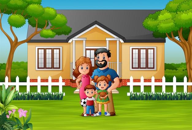 Heureuse famille debout devant la maison