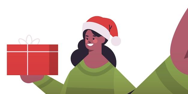 Heureuse femme afro-américaine en bonnet de noel avec des cadeaux tenant la caméra et prenant selfie nouvel an vacances de noël célébration concept illustration vectorielle portrait horizontal