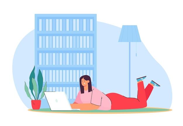 Heureuse femme allongée sur le sol avec un ordinateur portable et travaillant à domicile