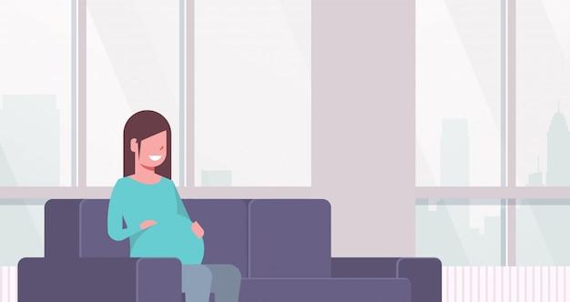 Heureuse femme enceinte assise sur le canapé fille