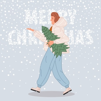 Heureuse femme marchant avec arbre de noël femme portant en bonnet de noel sur fond de neige