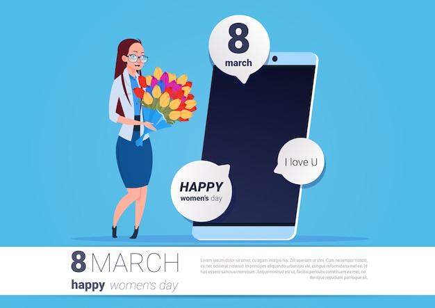 Heureuse femme tenir des fleurs debout sur téléphone intelligent avec message de souhaits 8 mars concept de vacances