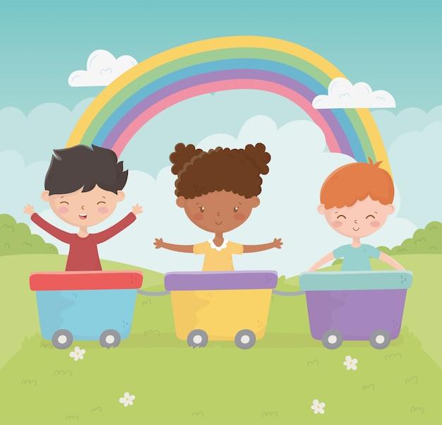 Heureuse fête des enfants souriante fille et garçon avec parc arc-en-ciel de jouet wagons