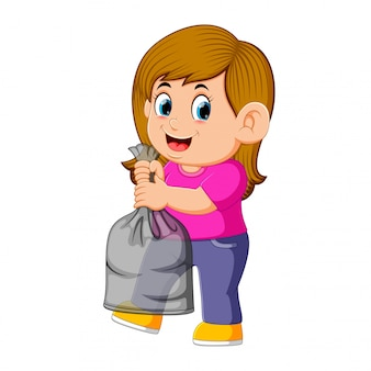 Heureuse jeune femme tenant un sac poubelle