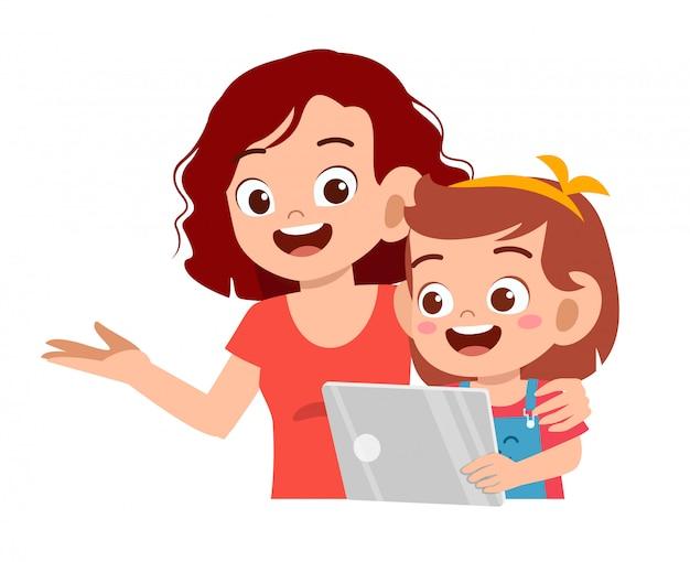 Heureuse jolie fille jouant à tablette avec maman