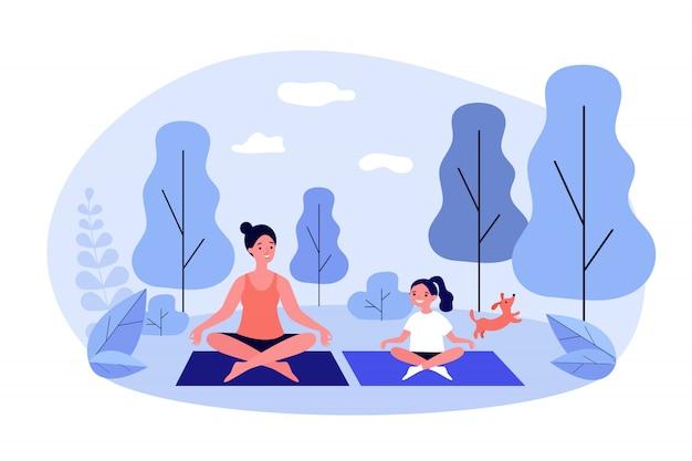 Heureuse maman et fille pratiquant le yoga dans le parc