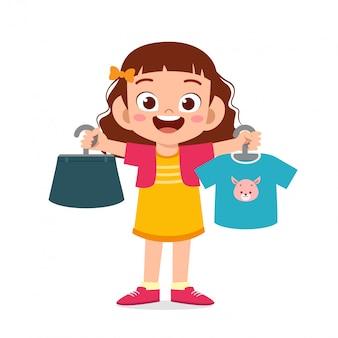 Heureuse mignonne petite fille enfant choisir des vêtements