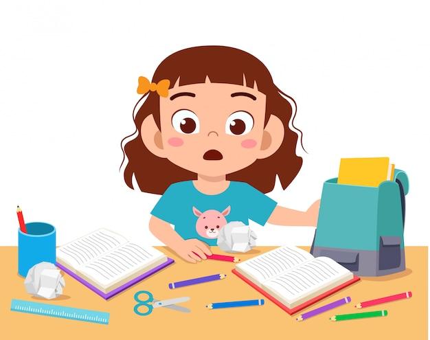 Heureuse petite fille mignonne avec un bureau en désordre