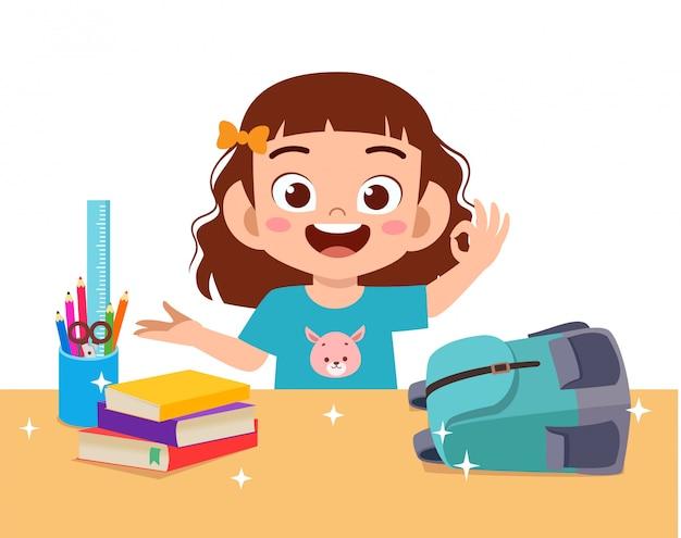 Heureuse petite fille mignonne avec un bureau propre