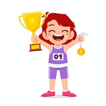 Heureuse petite fille mignonne tenant une médaille d'or et un trophée