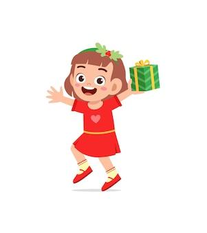 Heureuse petite fille tenant un cadeau pour noël