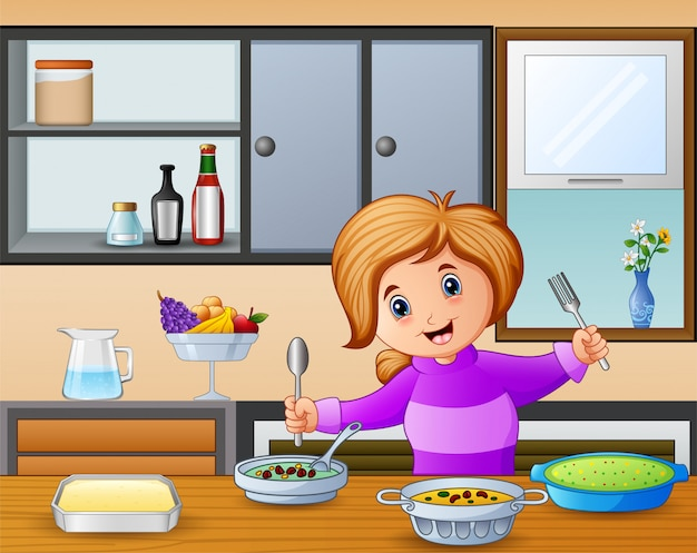 Heureuse petite fille tenant une cuillère et une fourchette à manger à la table