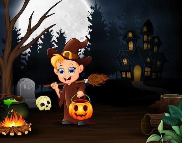Heureuse petite sorcière tenant un panier de citrouilles dans la nuit