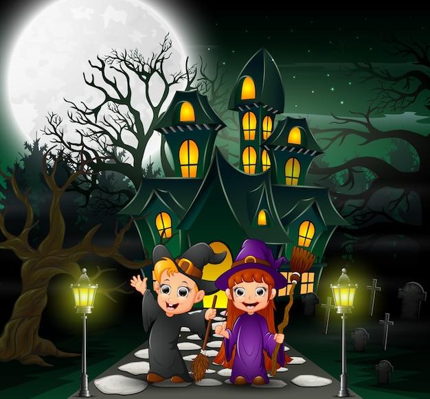 Heureux couple sorcière devant la maison hantée