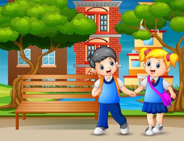 Heureux écoliers marchant passent dans le parc