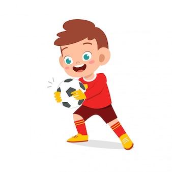 Heureux enfant garçon jouer au football comme gardien de but