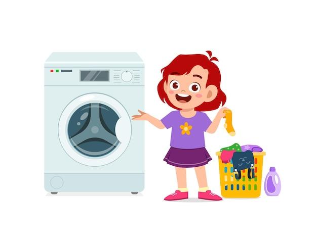 Heureux enfant mignon faire la lessive avec machine à laver