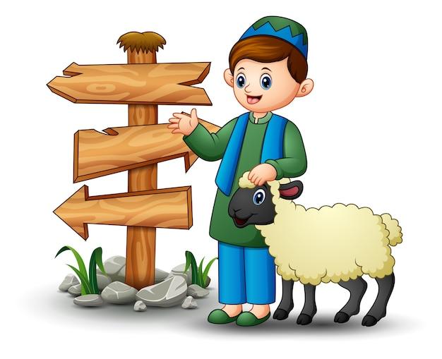 Heureux enfant musulman tenant des moutons avec signe de flèche en bois blanc